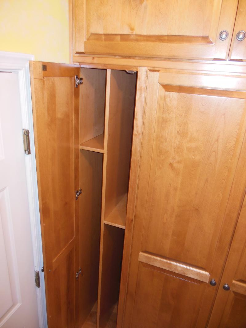Laundry room cabinet with custom dividers for brooms, ironing board or trays.